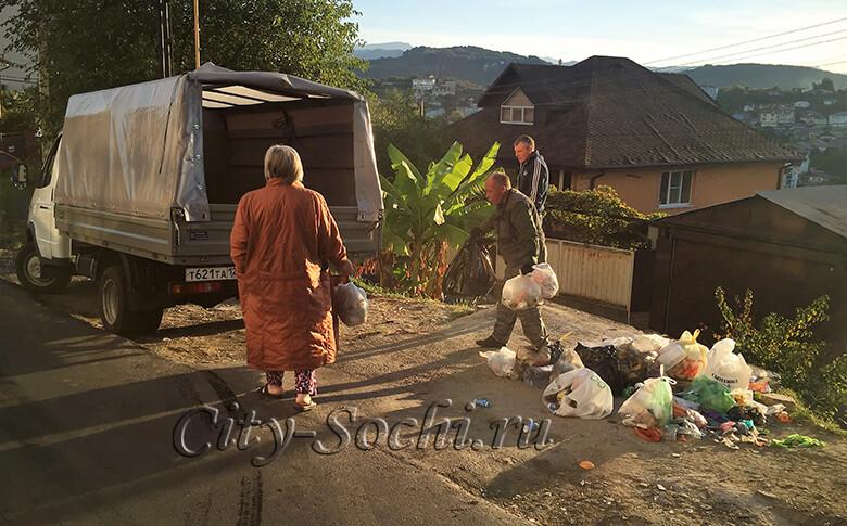 Работник САХ загружает мусор в машину